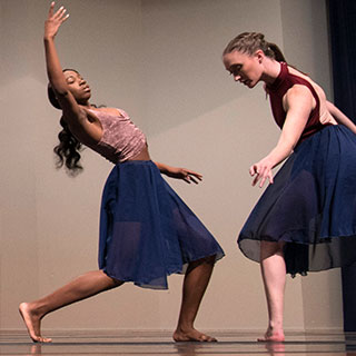 Two female students performing contemporary dance on stage.