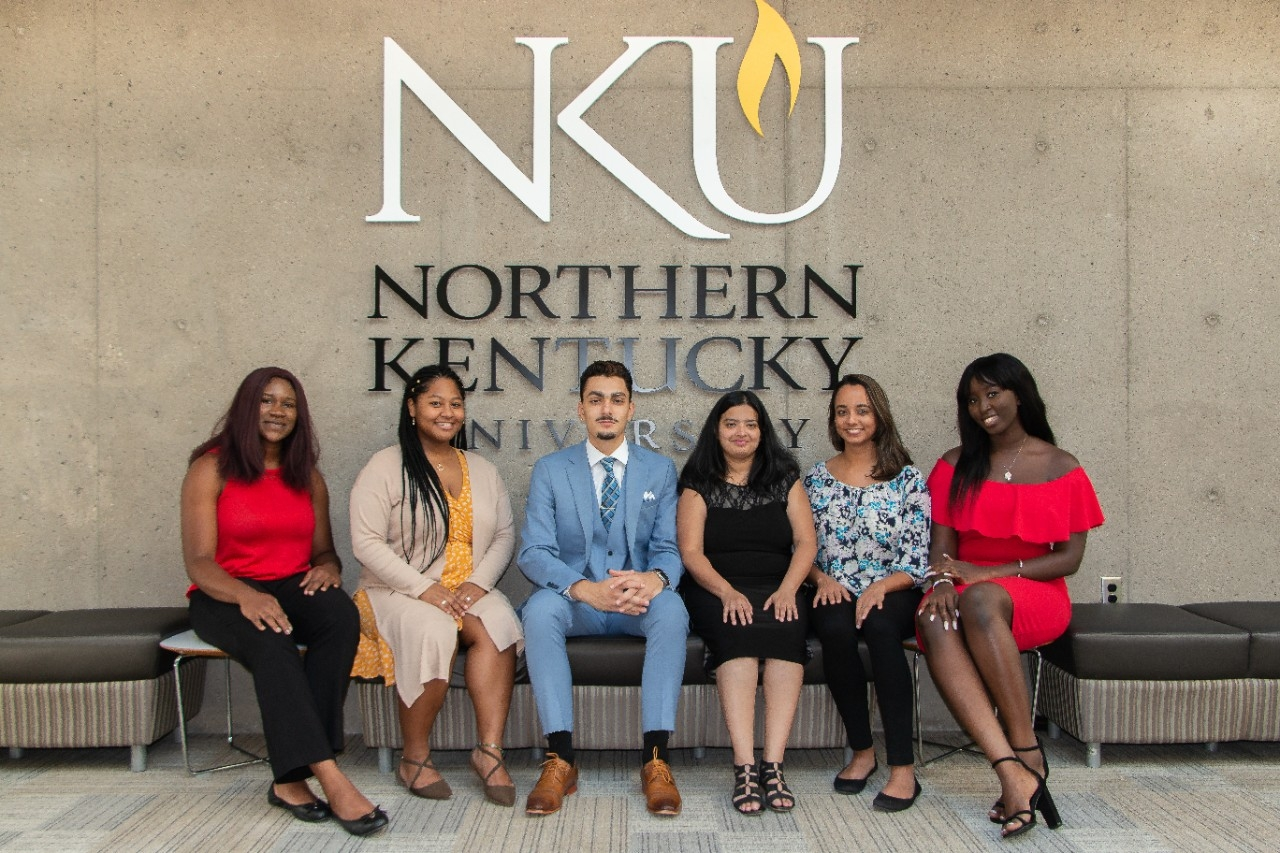 International students sitting in front of NKU logo
