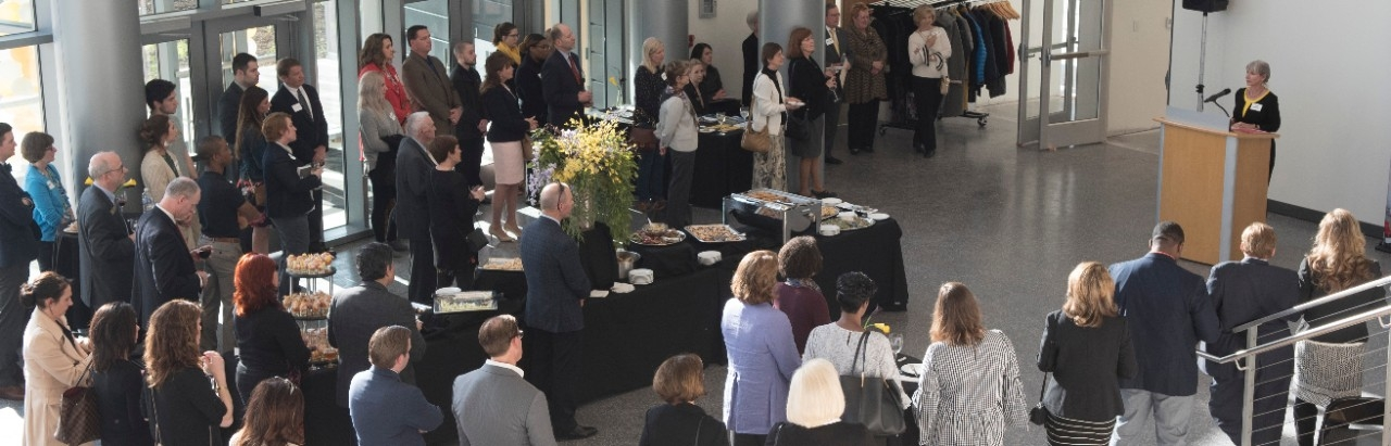 Event with speaker at podium, crowd of attendees and catered appetizers.