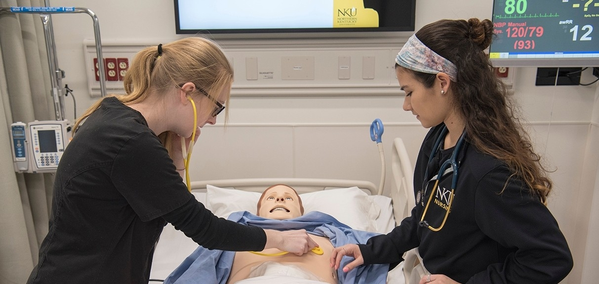 Students in Simulation Center working on simulation mannequin.